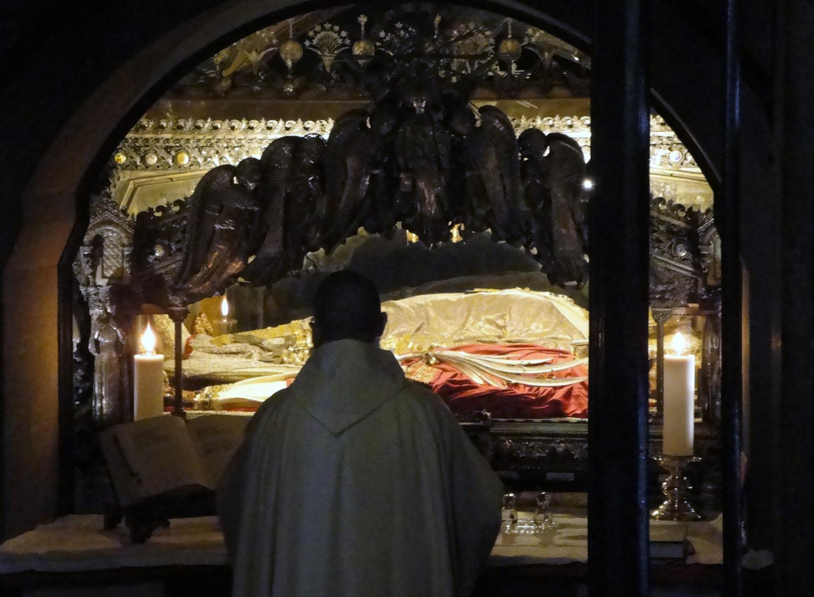A priest prays Mass at the tomb of Sts. Ambrose Gervasius and Protasius.  Ambrose is laid out in the center (wearing white) with the two saint martyrs at either side.