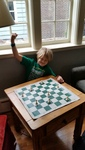 My son's triumphant strong arm gesture, sitting behind the chess puzzle he solved.