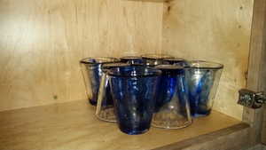 A set of blue conical juice glasses, stacked with one top-down and the next top-up so they fit neatly together.